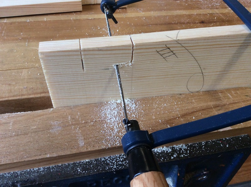 close up of sawing a finger joint on pine